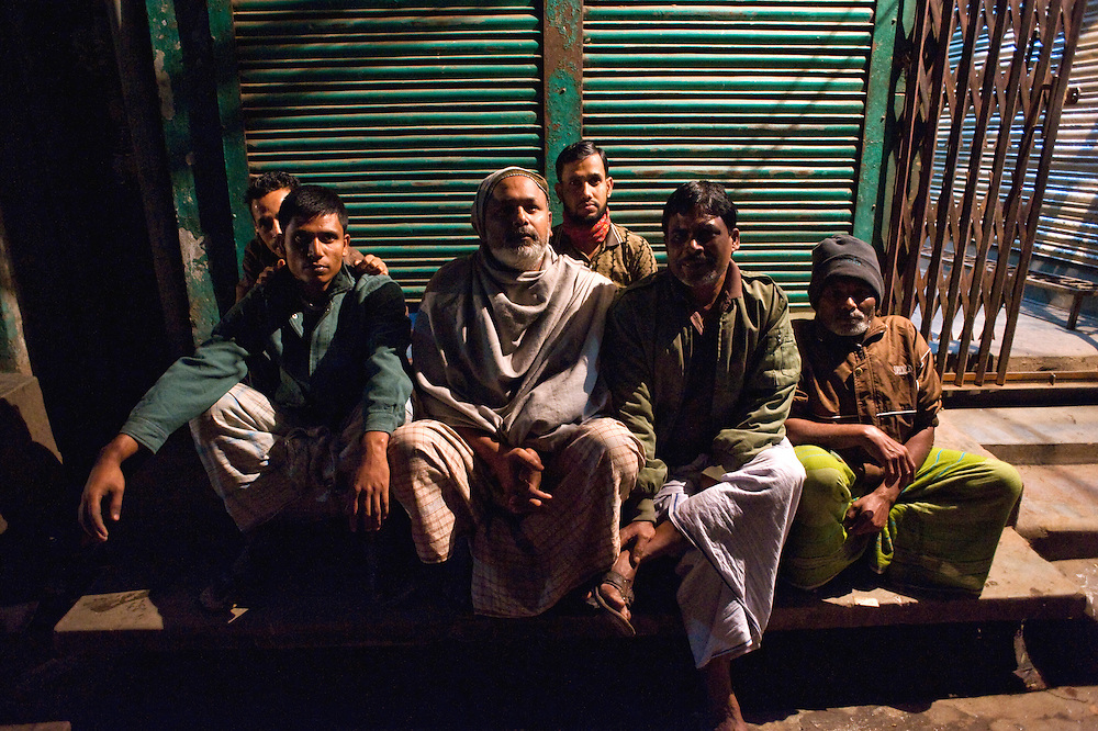 Shakari bazaar, Dhaka. It is midnight. Mohamed Nuru and his men wait for the streets to empty in order to start working.  They are 'nehari wallahs' or dust diggers.<br />