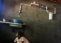 MISSION OF COMPASSION (WATER SYSTEM)<br /> Ayasha 7, retrieves a ball from under the sink of the Agape Home where team members from Faith International installed a water purification system.  The ultraviolet light treatment system will provide 360 gallons an hour of clean drinking water killing the pathogens responsible for the cholera and dysentery that claim so many lives in the region.