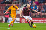 Steven Naismith (#14) of Heart of Midlothian runs past Steven Lawless (#15) of Livingston FC during the 4th round of the William Hill Scottish Cup match between Heart of Midlothian and Livingston at Tynecastle Stadium, Edinburgh, Scotland on 20 January 2019.