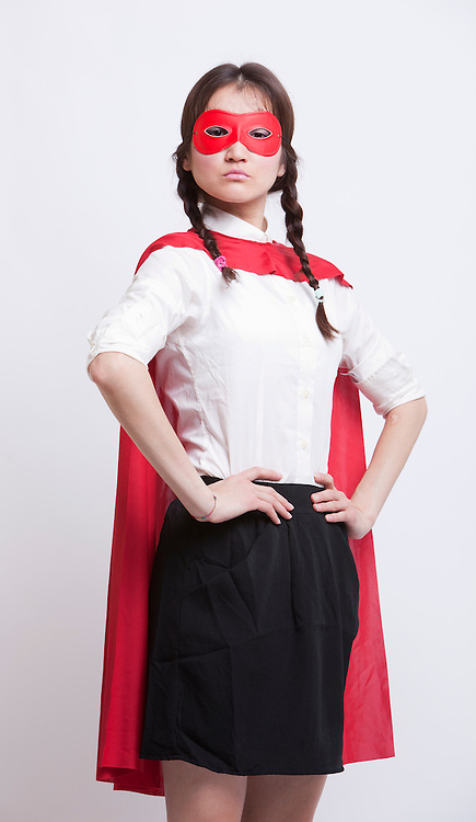 Portrait of young Asian woman in superhero costume with hands on hips against white background
