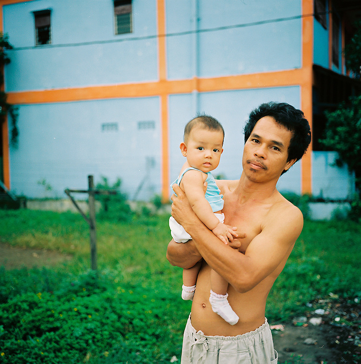 An Indonesian father holds his young son. <br /> Medan, Sumatra, Indonesia
