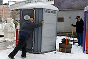 February 12, 2011 - Men place portable toilets in Chinatown Park in preparation for the Chinese New Year Celebration in Boston, MA. Photo by Lathan Goumas.