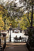 Couple on a bench at the Brouwersgracht where this canal crosses the Herengracht in Amsterdam.