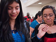 19 DECEMBER 2010 - PHOENIX, AZ: ELIZABETH HERNANDEZ, left, and CARMEN AMAYA, stand and pray during a prayer service for the DREAM Act in Phoenix. About 100 supporters of the DREAM Act gathered at First Congregational Church of Christ in Phoenix Sunday night, December 19, for a prayer vigil in support of the DREAM Act, which was defeated in the US Senate Saturday, Dec. 18. The DREAM Act, was supported by the Obama administration, and was an important part of the administration's immigration reform platform. The defeat of the DREAM Act, which would have established a path to citizenship for undocumented immigrants who were brought to the US by their parents when they were children, set back the President's immigration reform efforts.    PHOTO BY JACK KURTZ