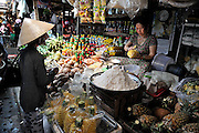 Woman skinning and decoratively carving pineapples. Cho Vung Tau (Vung Tau Market), Vung Tau, Vietnam