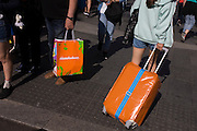 Matching coloured suitcase and shopping bag in a central London street.