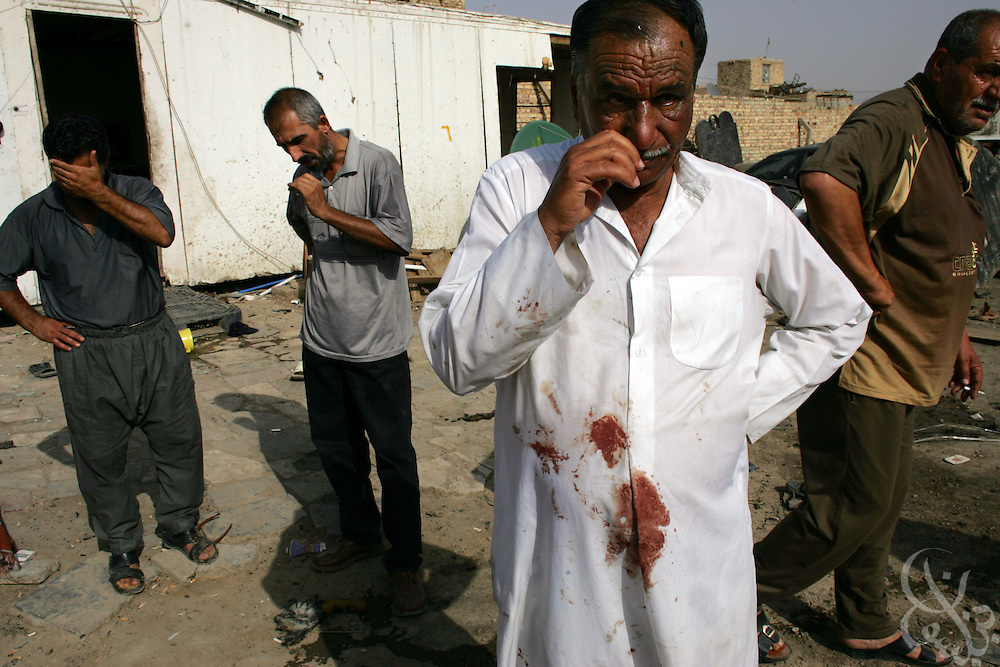 A blood stained Iraqi man and other witnesses mourn at the scene of a suspected sectarian attack that killed at least 18 and wounded 50 others in the neighborhood of Sha'ab in Northeastern Baghdad, Iraq, on Tuesday, May 16, 2006.