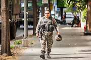 "20 MAY 2104 - BANGKOK, THAILAND: A Thai soldier walks along Ratchadamri Road after the declaration of martial law. The Thai Army declared martial law throughout Thailand in response to growing political tensions between anti-government protests led by Suthep Thaugsuban and pro-government protests led by the ""Red Shirts"" who support ousted Prime Minister Yingluck Shinawatra. Despite the declaration of martial law, daily life went on in Bangkok in a normal fashion. There were small isolated protests against martial law, which some Thais called a coup, but there was no violence.   PHOTO BY JACK KURTZ"