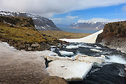 Thick sheets of ice line the river that flows into the Dynjandisvogur Fjord in Iceland's West Fjords.