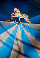 Chartres, France. Figure of colorful prancing pony on top of children's carousel at the fairground.