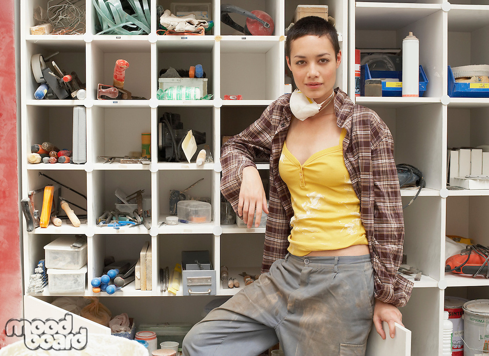 Young Woman leaning on Tool Shelves portrait