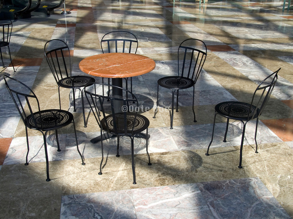 empty chairs placed around a small round table