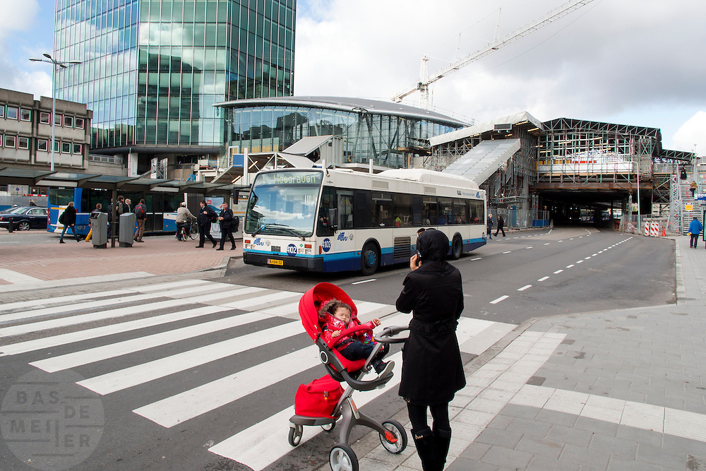 Een vrouw belt terwijl ze met een kind in een kinderwagen bij een zebrapad wacht tot een stadsbus is gepaseerd. In Utrecht wordt het centraal station grondig verbouwd. Momenteel is de tweede fase afgerond. De reizigers zullen nog tot 2016 last hebben van de verbouwing.<br /> <br /> A woman is on the phone while she is waiting with a child in a stroller for a bus to pass by. In Utrecht the central station is reconstructed. At this moment the second stage has finished. The travelers will be faced with inconveniences until 2016.