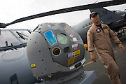 US Navy pilot and infra-red imaging camera on nose of a Sikorsky MH-60R helicopter at the Farnborough Airshow. ..The MH-60R is the U.S. Navy's newest and most advanced multi-mission helicopter, designed for anti-submarine and surface warfare (ASW/ASuW). Secondary missions include: Search and Rescue, anti-ship surveillance and targeting, communication relay and medevac/vertical replenishment. The Sikorsky-built helicipter with integrated avionics and mission systems by Lockheed Martin.