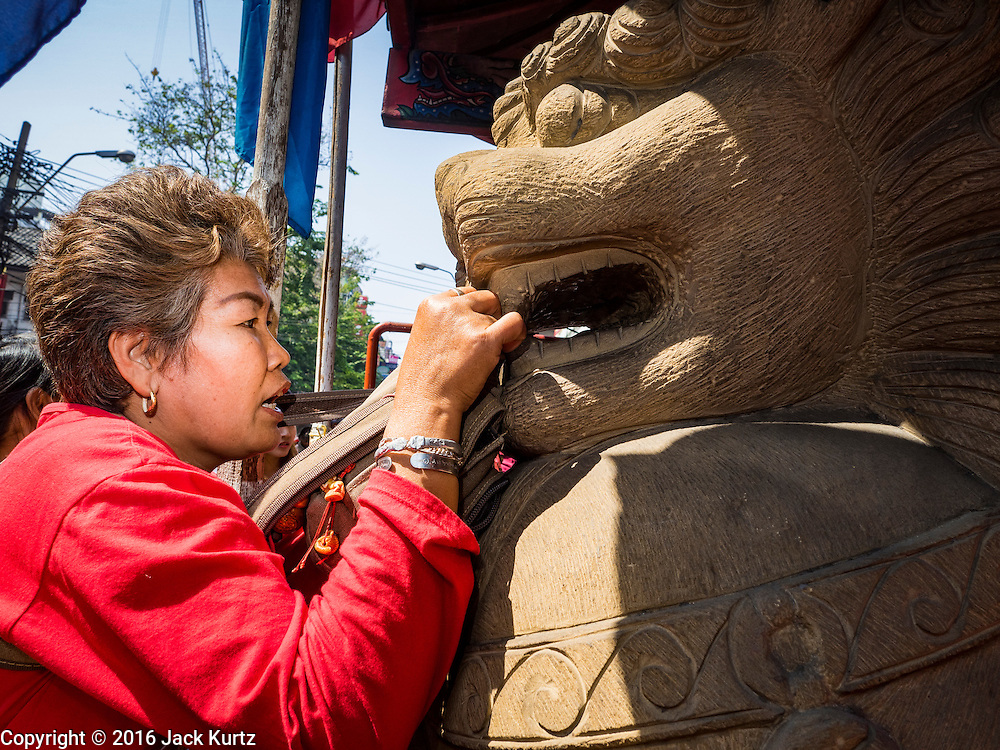 "08 FEBRUARY 2016 - BANGKOK, THAILAND: A woman makes a New Year's offering at the temple lions guarding Wat Mangon Kamlawat, the largest Mahayana (Chinese) Buddhist temple in Bangkok, in Bangkok's Chinatown district, during the celebration of the Lunar New Year. Chinese New Year is also called Lunar New Year or Tet (in Vietnamese communities). This year is the ""Year of the Monkey."" Thailand has the largest overseas Chinese population in the world; about 14 percent of Thais are of Chinese ancestry and some Chinese holidays, especially Chinese New Year, are widely celebrated in Thailand.       PHOTO BY JACK KURTZ"