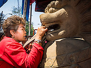 """08 FEBRUARY 2016 - BANGKOK, THAILAND: A woman makes a New Year's offering at the temple lions guarding Wat Mangon Kamlawat, the largest Mahayana (Chinese) Buddhist temple in Bangkok, in Bangkok's Chinatown district, during the celebration of the Lunar New Year. Chinese New Year is also called Lunar New Year or Tet (in Vietnamese communities). This year is the """"Year of the Monkey."""" Thailand has the largest overseas Chinese population in the world; about 14 percent of Thais are of Chinese ancestry and some Chinese holidays, especially Chinese New Year, are widely celebrated in Thailand.       PHOTO BY JACK KURTZ"""