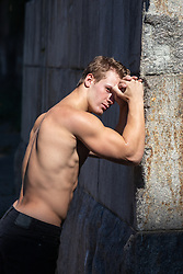 shirtless man against a stone wall