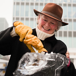 London, UK - 11 January 2012: a visitor scarves an ice block during the Ice sculpting festival 2013 in Canary Warf.