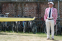 © Licensed to London News Pictures. 04/07/2018. Henley-on-Thames, UK. A man in rowing club colours stands next to a boat on day one of the Henley Royal Regatta, set on the River Thames by the town of Henley-on-Thames in England. Established in 1839, the five day international rowing event, raced over a course of 2,112 meters (1 mile 550 yards), is considered an important part of the English social season. Photo credit: Ben Cawthra/LNP
