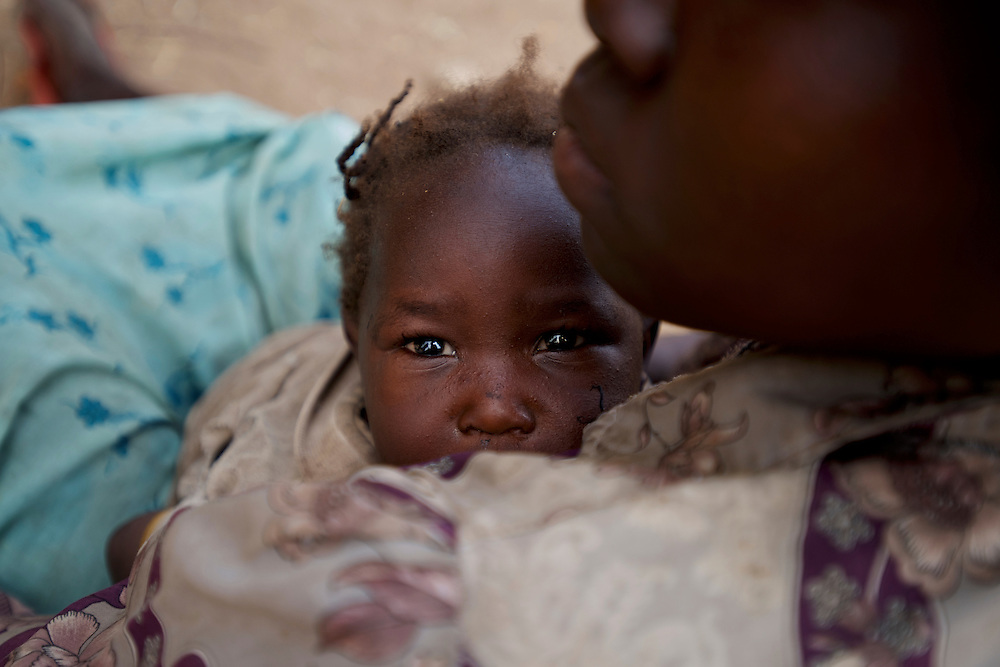 A mother carrying a baby rests under the shade of a tree before continue the three to four day journey to a refugee camp in the neighbour South Sudan.Thousands have fled the bombardments and hunger in South Kordofan.