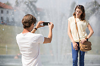 Young man photographing woman against fountain