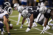 The Oakland Raiders defensive line gets set at the line of scrimmage opposite the Los Angeles Rams offensive line during the 2018 regular season week 1 NFL football game against the Los Angeles Rams on Monday, Sept. 10, 2018 in Oakland, Calif. The Rams won the game 33-13. (©Paul Anthony Spinelli)