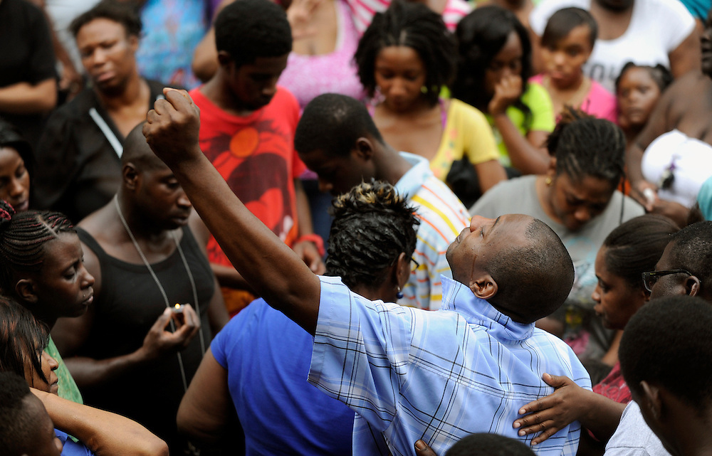 Darryl Preston, Javon Neal's uncle, holds his fist in the air during a candle-light vigil Monday, July 23, 2012 in Tampa. Police say on Sunday Javon, 16, ran from officers up a stairwell then whirled around brandishing a pistol grip, pump-action shotgun before police shot him.