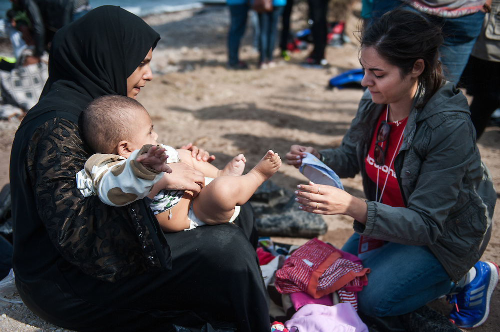 Constantina Strikou, programme coordinator of ActionAid Hellas, helps aSyrian girls to change her wet clothes at the beach of Skala Sykamias, Lesvos, Greece.