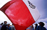 FEB 24, 2001 - SAN CRISTOBAL DE LAS CASAS, CHIAPAS, MEXICO: Supporters of  the EZLN (Zapatistas) wave a Mexican flag during a pro-Zapatista rally on the Zocalo in San Cristobal de las Casas, Chiapas, Mexico, Feb. 24, 2001. The rally was to mark the beginning of the Zapatista's caravan from San Cristobal de las Casas to Mexico City. About 3,000 Zapatistas participated in the march through San Cristobal. The Zapatistas went to Mexico City to press their demands for the passage of the San Andres Accords, signed between the Zapatistas and the Mexican government in 1996 but stalled in the Mexican congress by the formerly ruling Institutional Revolutionary Party.  © Jack Kurtz  INDIGENOUS   WAR  POVERTY  HUMAN RIGHTS  CIVIL RIGHTS   GLOBALIZATION     PATRIOTISM
