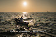 A Panamanian fisherman paddles a small boat at sunrise in Panama Bay.