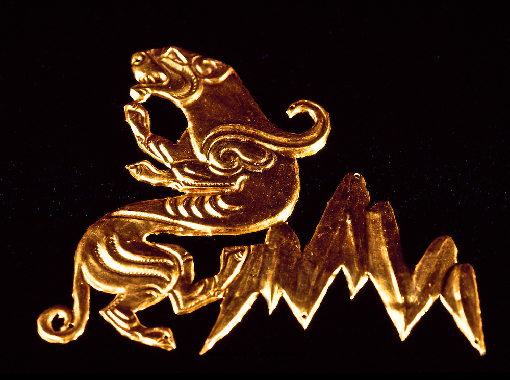 Golden Warrior headdress decoration stamped and engraved gold plaque that features mountains and snow leopard.  Museum of Archeology, Almaty, Kazakhstan