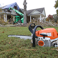 A chainsaw waits to be used again as others rush to seal up the south wall of a home along Market Street in Charleston Gardens in Tupelo.