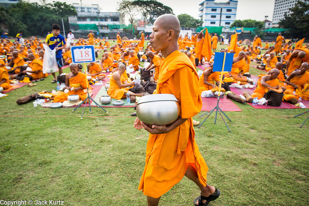 26 JANUARY 2013 - BANGKOK, THAILAND:  A Buddhist monk walks through the monks' camp at Surasakmontri School before the monks resumed their mass pilgrimage through Bangkok. 1,128 Buddhist monks from the Dhammakaya movement took part in a 25-day pilgrimage walk passing through Bangkok and several provinces in central Thailand, as part of a voluntarily undertaking of ascetic practices. The pilgrimage is scheduled to end Sunday, January 27 at Wat Phra Dhammakaya near Bangkok. Along the way Thai Buddhists laid marigolds along their path and greeted them for merit making. The Dhammakaya is the fastest growing Buddhist movement in Thailand. The pilgrimage is reported to be the largest pilgrimage in Thailand and organizers hope to get it placed in the Guiness World Records book.     PHOTO BY JACK KURTZ