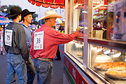 "01 SEPTEMBER 2011 - ST. PAUL, MN:  High School rodeo participants buy food at a booth on the midway at the Minnesota State Fair. The Minnesota State Fair is one of the largest state fairs in the United States. It's called ""the Great Minnesota Get Together"" and includes numerous agricultural exhibits, a vast midway with rides and games, horse shows and rodeos. Nearly two million people a year visit the fair, which is located in St. Paul.   PHOTO BY JACK KURTZ"