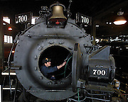 Jim Vanderbeck cleans out the smoke box of steam locomotive SP&S 700 at the Brooklyn roundhouse currently under preparation for its trips to Spokane. Vanderbeck is a member of the Pacific Railroad Preservation Association.