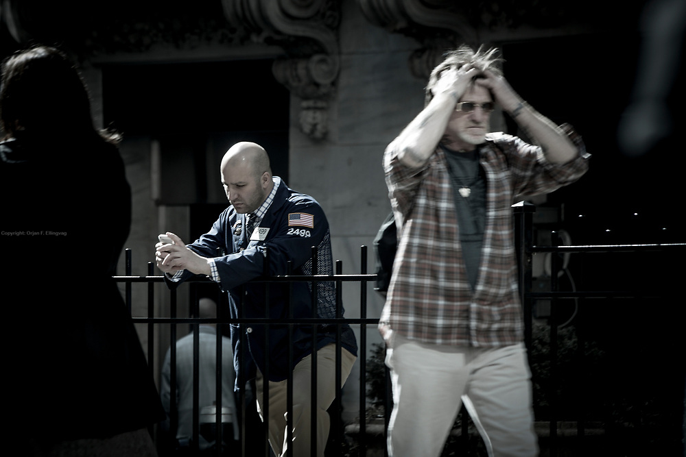 A floor trader takes a  break outside tne NYSE Euronext Stock Exchange on Wall Street while another man pulls his hair while walking past him.