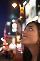 Young Woman on Sidewalk at Night Looking Up