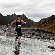 Runner Johanna Edis crosses Moke Creek on the Ben Lomond High Country Station during the Pure South Shotover Moonlight Mountain Marathon and trail runs. Moke Lake, Queenstown, New Zealand. 4th February 2012. Photo Tim Clayton