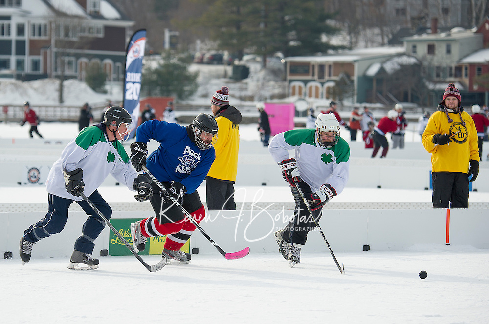 "Local teams REMax Hackers and the Puck Nuts go for the puck during first round ""Just for Fun"" division at Meredith Bay during the New England Pond Hockey Classic Friday morning.  (Karen Bobotas/for the Laconia Daily Sun)"