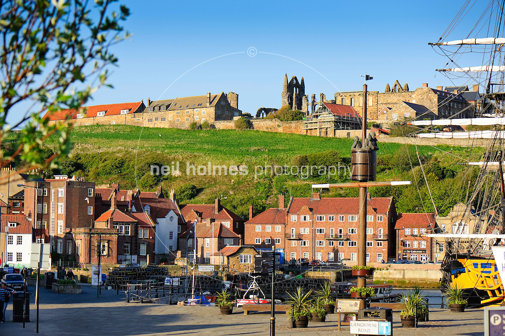Whitby town centre bathed in spring evening sunshine across the harbour marina and the ruins of the Abbey on the hillside.
