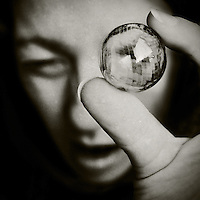 close-up of a girl's face holding a glass bead