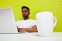 Indian man working at his desktop with mug in focus in foreground