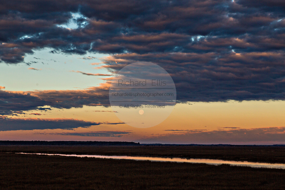 Sunrise over the Edisto River and marsh as the moon sets in Edisto Island, South Carolina.