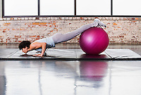 A young woman doing pushups on a mat in a healthclub while balancing her legs / feet on a exercise ball.