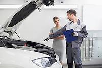 Young male repairman explaining car engine to female customer in automobile repair shop