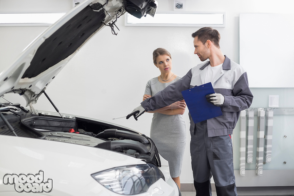 Young male repairman explaining car engine to female customer in automobile repair shop