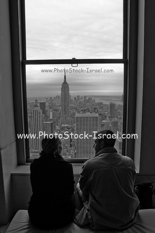 USA, NY, New york city, Manhattan, A couple in their hotel room sitting on a bed looking out at the skyline. Black and white