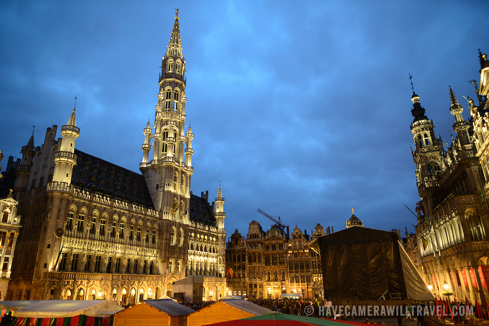 Grand Place, Brussels, at dusk. Originally the city's central market place, the Grand-Place is now a UNESCO World Heritage site. Ornate buildings line the square, including guildhalls, the Brussels Town Hall, and the Breadhouse, and seven cobbelstone streets feed into it.