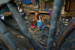 Kolkata's (Calcutta) poorest residents, the hand rickshaw pullers begin to wake around 5 am inside their dheera, a small home where they sleep together on Ali Muddin Street, August 31, 2007. This congested city was the first city of the colonial British and  now it is the only city of India where hand pulled rickshaws are still being pulled. In 1996, the Government of West Bengal announced that it was intending to ban the rickshaws to relieve traffic congestion  but it never was fully enforced. In 2007, the government again pushed to have the ban enforced and a case is currently being decided in the Supreme court that will determine the outcome for the hand pulled rickshaws.