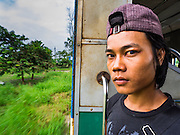 26 OCTOBER 2015 - YANGON, MYANMAR:  A man stands in the doorway on the Yangon Circular Train. The Yangon Circular Railway is the local commuter rail network that serves the Yangon metropolitan area. Operated by Myanmar Railways, the 45.9-kilometre (28.5 mi) 39-station loop system connects satellite towns and suburban areas to the city. The railway has about 200 coaches, runs 20 times daily and sells 100,000 to 150,000 tickets daily. The loop, which takes about three hours to complete, is a popular for tourists to see a cross section of life in Yangon. The trains run from 3:45 am to 10:15 pm daily. The cost of a ticket for a distance of 15 miles is ten kyats (~nine US cents), and for over 15 miles is twenty kyats (~18 US cents).       PHOTO BY JACK KURTZ